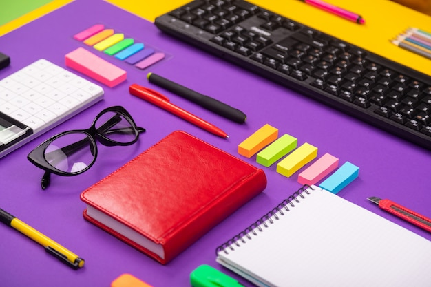 Local de trabalho moderno com teclado, diário, lápis, canetas e óculos em laranja-roxo.