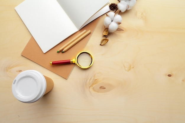 Local de trabalho moderno de cor bege na mesa de madeira com muitas coisas nele. vista do topo