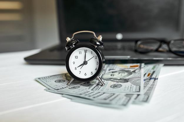 Local de trabalho moderno de laptop, relógio, dinheiro, notas de dólares com espaço de cópia em fundo branco de madeira. tempo para dinheiro.