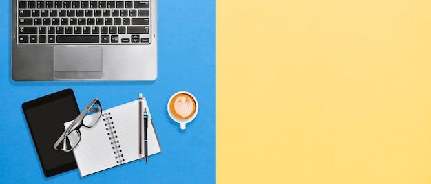 Local de trabalho moderno do desktop do escritório com espaço da cópia no fundo amarelo e azul brilhante
