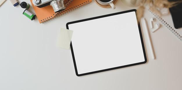 Local de trabalho motivado fotógrafo com tablet de tela em branco