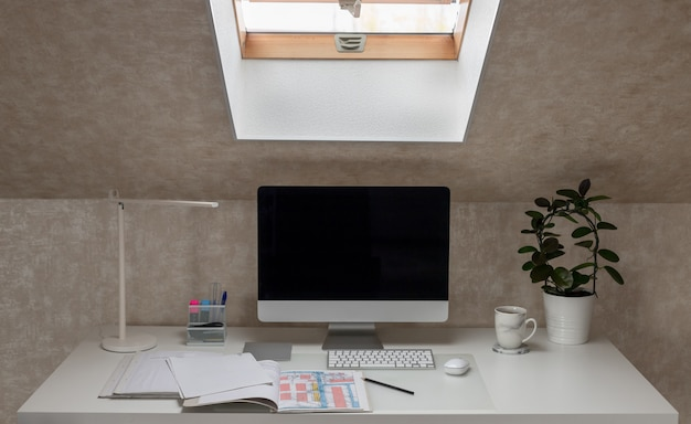 Local de trabalho no computador desktop do escritório em casa, lâmpada de mesa, pastas abertas com documentos e uma xícara de café conceito de quarentena de coronavírus