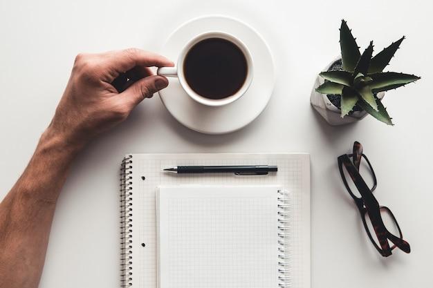Local de trabalho remoto com mão de homens, teclado, xícara de café e bloco de notas.