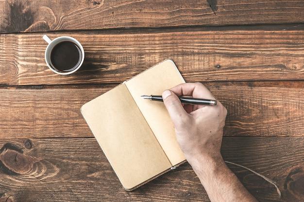 Local de trabalho simples. mesa de madeira da mesa de escritório, com a mão escrevendo em um caderno vazio e café.