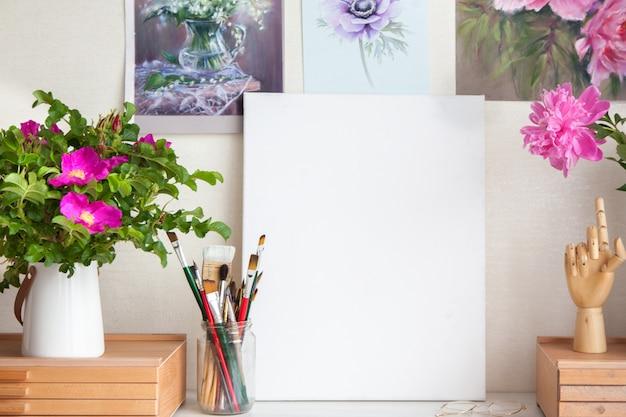 Local de trabalho vazio de artista mulher ao lado de materiais para desenhar pincéis, lápis e pinturas de belas flores cor de rosa na parede. lugar para texto. tela branca limpa