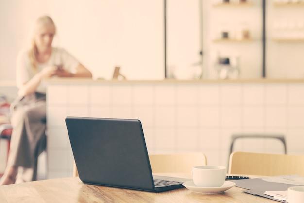 Local de trabalho vazio no espaço de co-trabalho. mesa redonda com laptop, xícaras de café e documentos
