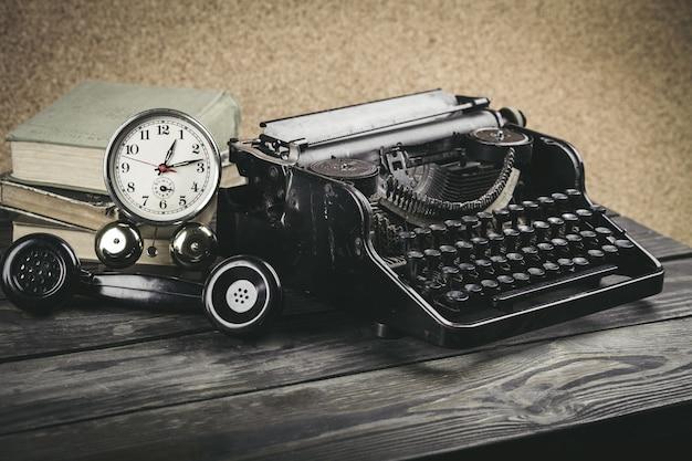 Local de trabalho vintage com máquina de digitação, telefone e relógio na mesa