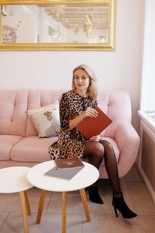 Localização bonita mulher sorridente no sofá. jovem mulher segurando um livro nas mãos dela