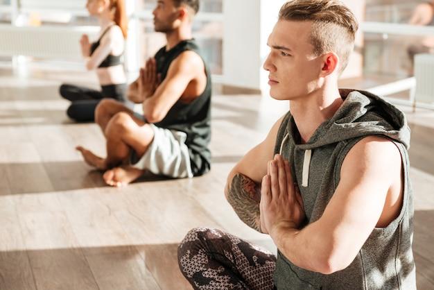 Localização de homem em pose de lótus e fazendo yoga no estúdio