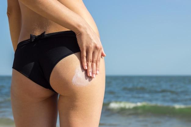Loção bronzeadora mulher aplicar creme solar protetor solar. linda linda garota aplicando bronzear creme na pele na praia. bronzeamento de sol. cuidados com a pele e proteção. período de férias