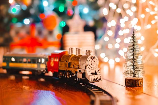Locomotiva a vapor vintage de brinquedo no chão sob uma árvore de natal decorada em um fundo de guirlanda de luzes de bokeh