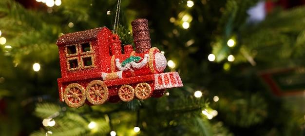 Locomotiva de brinquedo de vidro vermelho brilhante pendurada na árvore de natal com uma guirlanda
