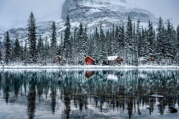 Lodge de madeira na floresta de pinheiros, com reflexo de neve pesada no lago