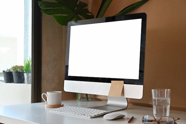 Loft com moderno computador de mesa e suprimentos