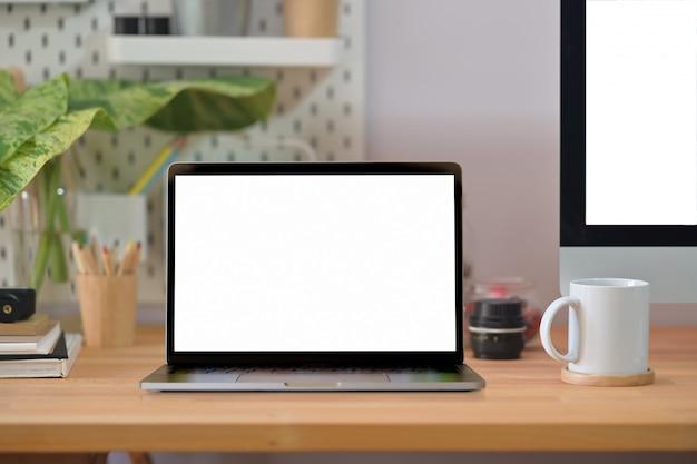 Loft mesa de mesa de escritório de madeira com laptop, cartaz, caneca de café e suprimentos.
