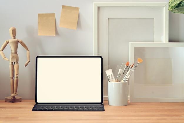 Loft mesa de mesa de escritório de madeira com tablet, cartaz e suprimentos.