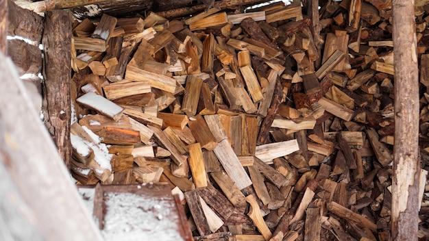 Log na aldeia. troncos cortados sob uma cobertura no inverno. fundo de madeira natural.