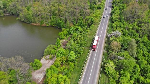 Logística de transporte com caminhões em uma rodovia entre a floresta verde e o lago