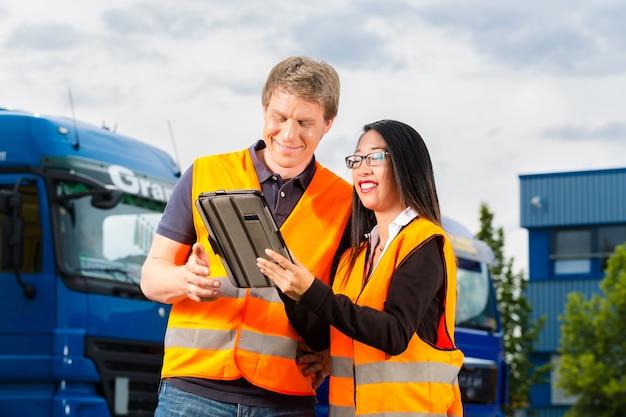 Logística - motorista orgulhosa ou despachante e colega de trabalho com tablet, na frente de caminhões e reboques, em um ponto de transbordo, é uma equipe boa e bem-sucedida