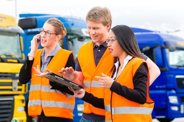 Logística - motorista orgulhoso ou despachante e colegas com computador tablet, na frente de caminhões e reboques, em um ponto de transbordo, é uma equipe boa e bem-sucedida