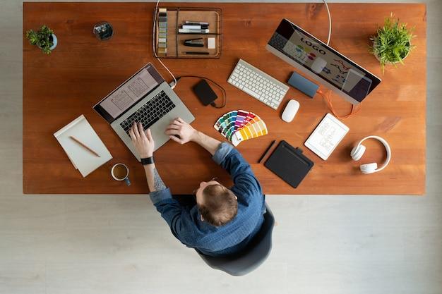 Logo acima, a visão de um homem com tatuagem sentado à mesa de madeira e editando o design da interface do usuário no laptop