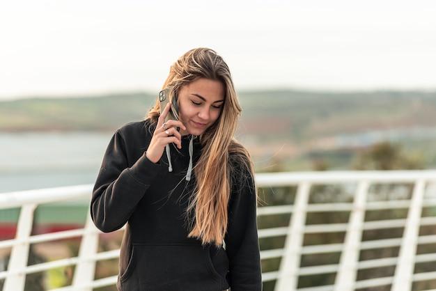 Loira adolescente fazendo uma ligação em seu telefone celular enquanto caminhava em uma ponte urbana branca.