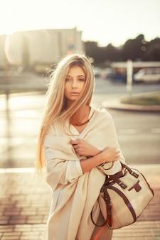 Loira adolescente segurando a bolsa com fundo borrado