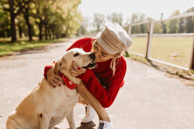 Loira adorável beijando seu cachorro com ternura no caminho do parque outono. menina elegante se sente bem sob o sol.