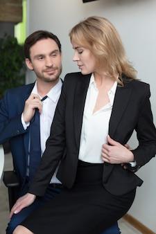 Loira adorável flerta com o chefe no escritório, sentado no colo