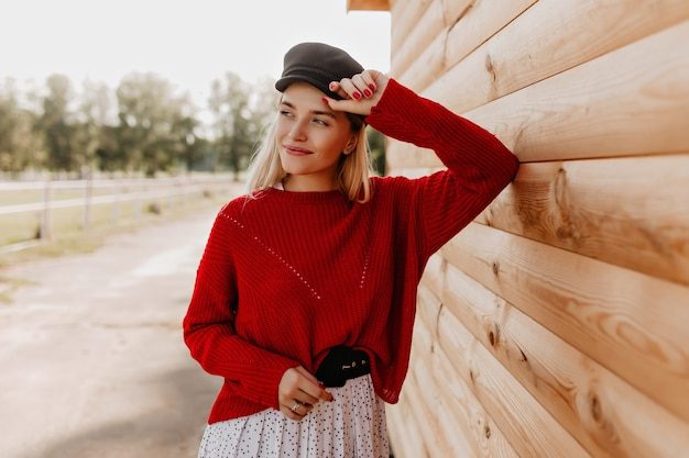 Loira adorável sorrindo alegremente perto da casa de madeira no parque. linda garota posando com as roupas da estação do lado de fora.