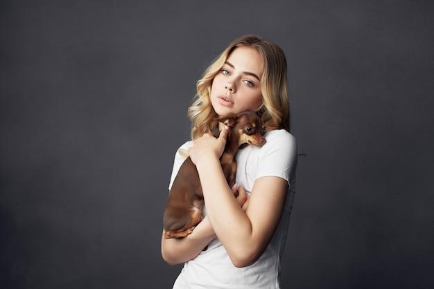 Loira alegre com um cachorrinho nas mãos de um animal chihuahua amigo
