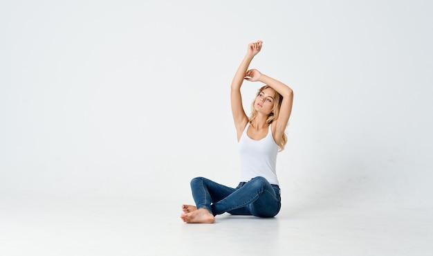 Loira alegre sentada no chão fazendo emoções de estilo de vida