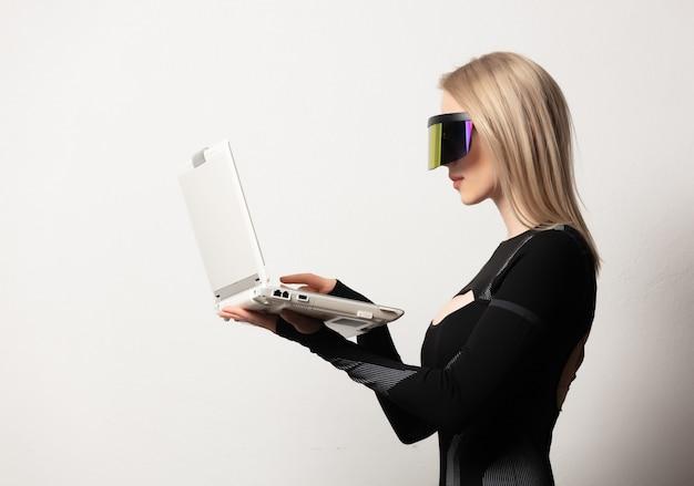 Loira andróide feminina em óculos vr e laptop em fundo branco.