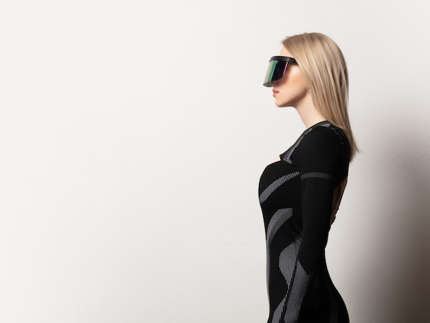 Loira andróide feminina em óculos vr e terno em fundo branco.