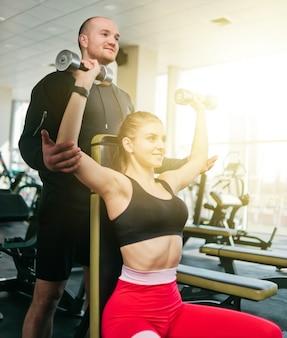 Loira apta a mulher em roupas esportivas, fazendo supino com halteres acima da cabeça, enquanto está sentado em um banco com um instrutor de parceiro masculino no ginásio.