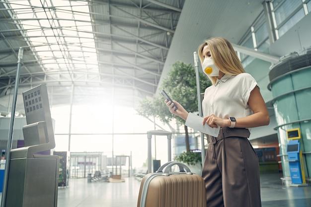 Loira atraente de cabelos compridos usando máscara protetora durante o voo de negócios durante o período de quarentena