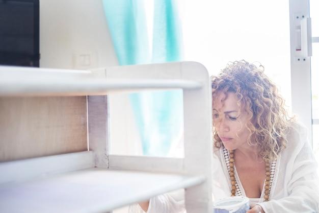 Loira atraente jovem encaracolada em casa trabalhando em uma pintura e restauração de móveis brancos. concentrada enquanto trabalhava em um quarto branco de sua casa. conceito de atividade interna de passatempo e lazer para nice