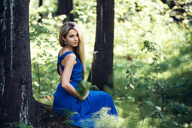 Loira atraente linda em um vestido azul longo sozinho na floresta. menina sentada em uma árvore e sonhos