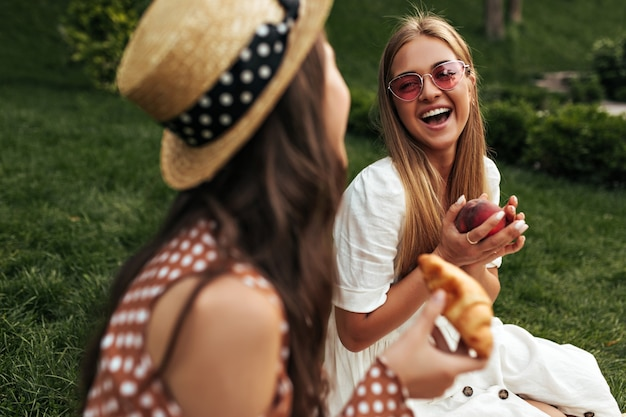 Loira bem humorada e bronzeada, com elegantes óculos escuros vermelhos e vestido branco, ri, fala com a amiga e segura maçã