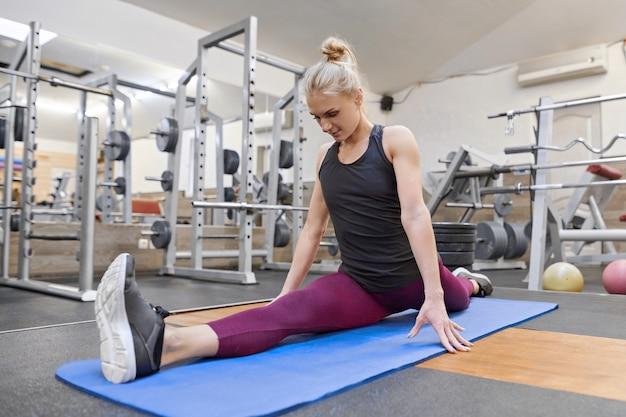 Loira bonita adulta feminina fazendo alongamento praticando ioga no ginásio