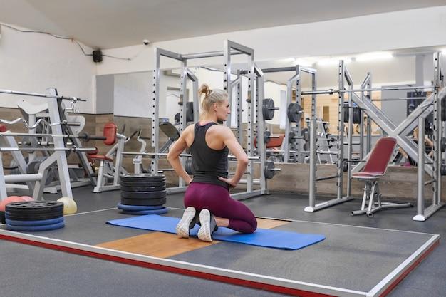 Loira bonita adulta feminina fazendo alongamento praticando ioga