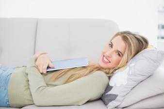Loira bonita alegre segurando seu tablet deitado no sofá aconchegante