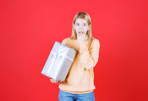 Loira bonita colocando a mão perto do queixo enquanto segura a caixa de presente na frente da parede vermelha