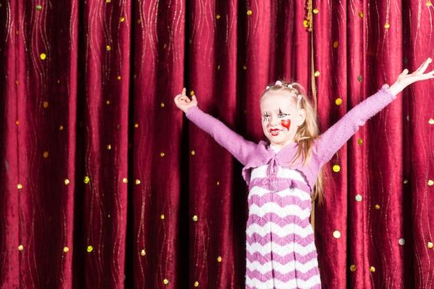 Loira bonita com fantasia de pantomima em pé no palco tocando para o público com os braços estendidos e um grande sorriso