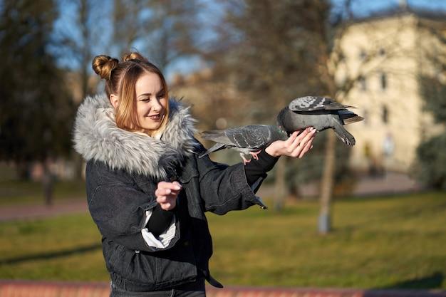 Loira bonita elegante alimentando pombos da mão.