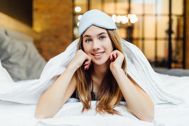 Loira bonita em sua cama de pijama azul e máscara de dormir.