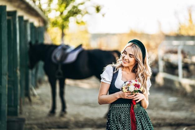 Loira bonita em vestidos casuais, vestido tradicional oktoberfest em pé na fazenda perto da porta de madeira