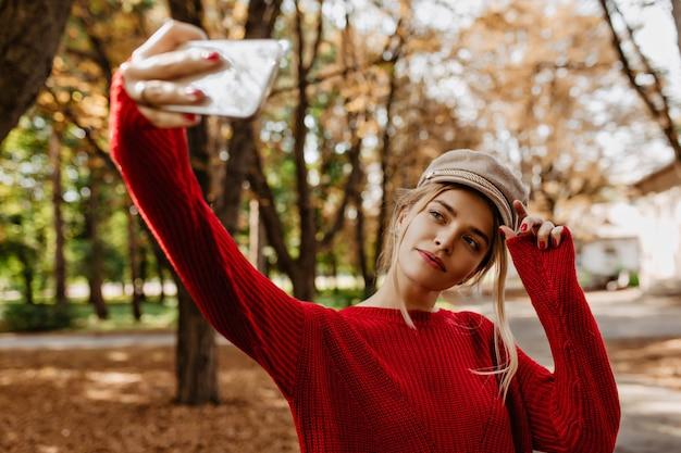 Loira bonita fazendo selfie no parque outono. uma senhora encantadora de suéter vermelho e chapéu branco faz fotos.