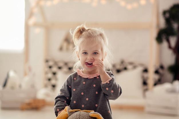 Loira bonita feliz deovchka 2-3 anos andando em uma sala em um brinquedo de elefante e ri