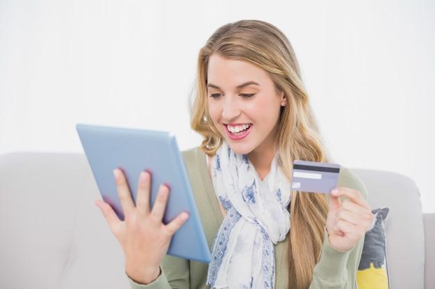 Loira bonita feliz usando seu cartão de crédito para comprar on-line